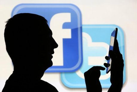A man is silhouetted as he uses a mini tablet computer while standing in front of a video screen with the Facebook and Twitter logos, in thi