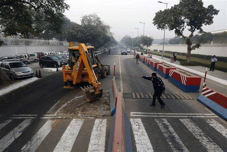 A traffic policeman guides a bulldozer removing the security barriers in front of the U.S. embassy in New Delhi December 17, 2013. REUTERS/A