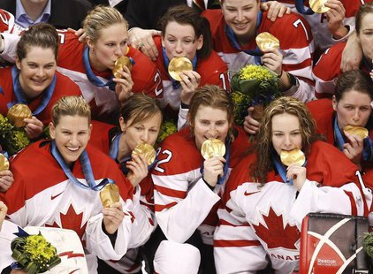 Canadian hockey team members pose with their gold medals after defeating the U.S. in their gold medal ice hockey game at the Vancouver 2010