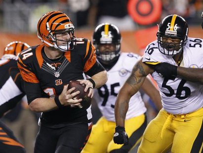 Cincinnati Bengals quarterback Andy Dalton (14) throws under pressure from the Pittsburgh Steelers' LaMarr Woodley (56) and Jarvis Jones (95