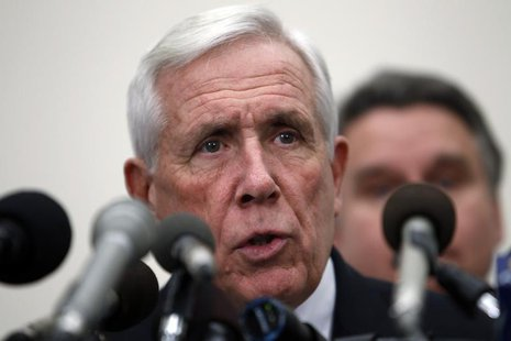 U.S. Representative Frank Wolf (R-VA) speaks with Rep. Chris Smith (R-NJ) (obscured) during a news conference on Capitol Hill in Washington,