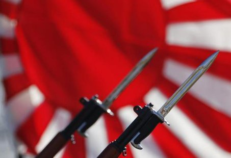 Bayonets attached to rifles used by Japanese Self-Defense Forces are seen in front of Japan's rising sun flag, which is used by the forces, during the annual troop review ceremony at Asaka Base in Asaka, near Tokyo October 27, 2013. CREDIT: REUTERS/ISSEI KATO