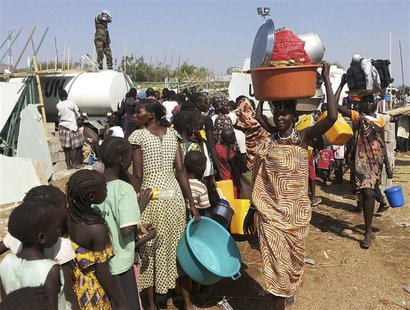 Civilians arrive to a shelter at the United Nations Mission in the Republic of South Sudan (UNMISS) compound on the outskirts of the capital