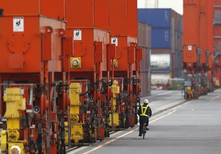 A man rides a bicycle past containers at a port in Tokyo October 21, 2013. REUTERS/Issei Kato
