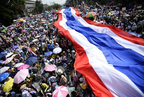 Anti-government protesters unveil a large Thai flag as they descend on Government House in Bangkok December 9, 2013. REUTERS/Dylan Martinez