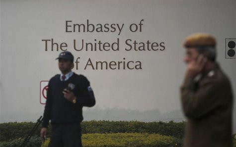 A U.S. embassy security guard (L) and an Indian policeman stand in front of the main gate of the embassy as the bulldozer (unseen) removes t