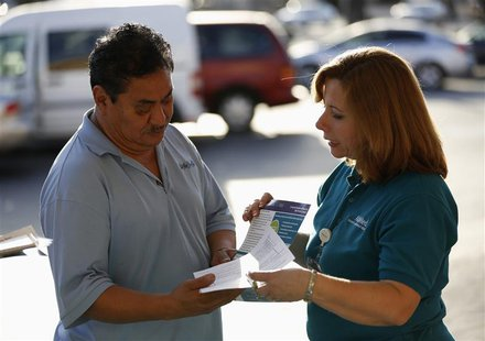 Engrith Acosta, patient care coordinator at AltaMed, speaks to a man during a community outreach on Obamacare in Los Angeles, California Nov