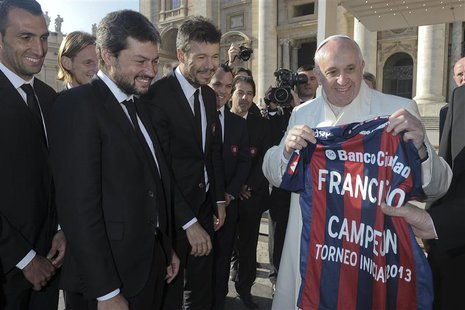 Pope Francis holds a jersey of Argentine soccer team San Lorenzo, given to him as a gift from members of the team, during the Wednesday gene