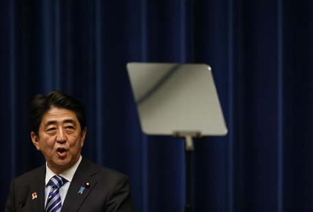 Japan's Prime Minister Shinzo Abe looks at a prompter as he speaks during a news conference to wrap up the ASEAN-Japan Commemorative Summit
