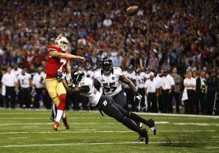 San Francisco 49ers quarterback Colin Kaepernick (L) throws under pressure from Baltimore Ravens free safety Ed Reed during the first quarte
