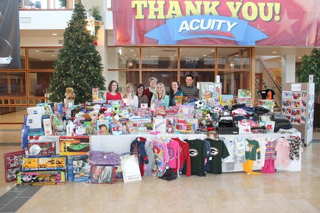 ACUITY employees stand by some of the donations made to this year's holiday gift drive.