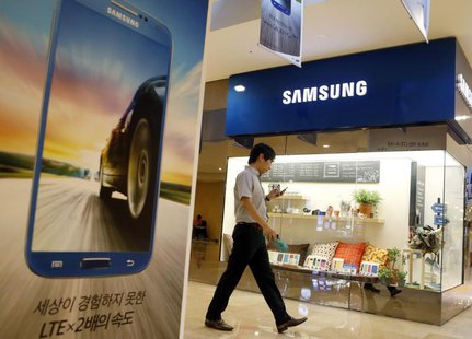 A man using his mobile phone walks past a Samsung Electronics shop in the company's main office building in central Seoul July 23, 2013. REU