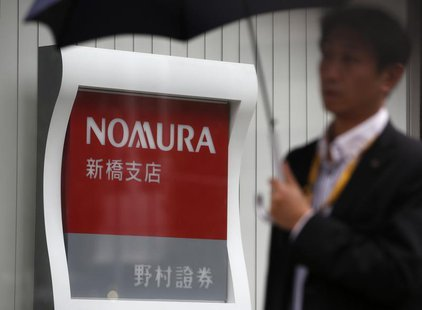A man holding an umbrella walks past a signboard of Nomura Securities outside its branch in Tokyo October 29, 2013. REUTERS/Issei Kato