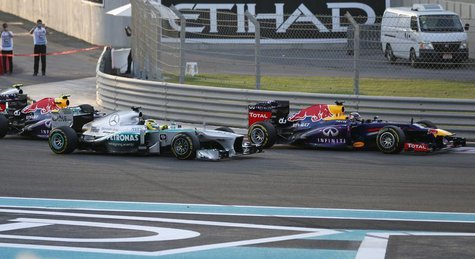 Red Bull Formula One driver Sebastian Vettel of Germany (R) drives ahead of Mercedes Formula One driver Nico Rosberg of Germany and Red Bull