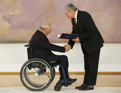 Wolfgang Schaeuble (L) receives his certificate of appointment as Finance Minister from President Joachim Gauck during a ceremony in the Bel