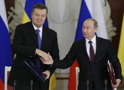Russia's President Vladimir Putin (R) shakes hands with his Ukrainian counterpart Viktor Yanukovich during a signing ceremony after a meetin