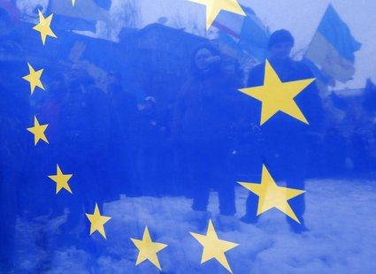 Pro-European integration protesters are seen through an EU flag during a rally near the Interior Ministry headquarters in Kiev December 17,