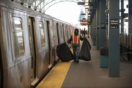 A custodian carries bags of garbage as New York City subway trains stop at the Coney Island station prior to a total subway shutdown at 7pm