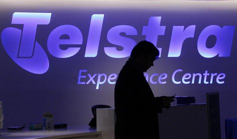 A man uses his mobile phone in front of a Telstra logo in central Sydney August 13, 2009. REUTERS/Daniel Munoz