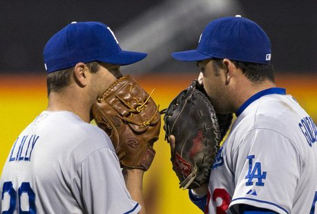 Los Angeles Dodgers starting pitcher Ted Lilly and first baseman Adrian Gonzalez (R) use their gloves to hide their conversation on the moun