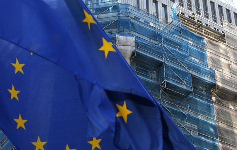 A European Union flag flutters as a construction worker is seen on a building under renovation in Brussels December 9, 2013. REUTERS/Francoi