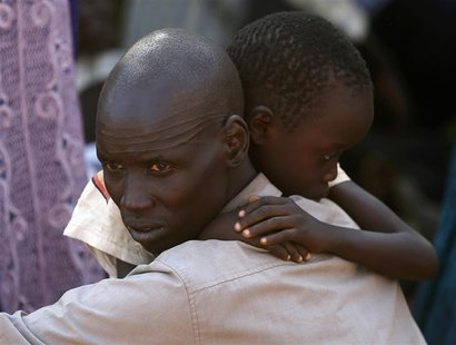 An internally displaced man holds his son inside a United Nations Missions in Sudan (UNMIS) compound in Juba December 19, 2013. REUTERS/Gora