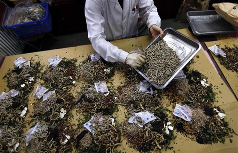 A worker prepares traditional Chinese herbal medicines at Beijing's Capital Medical University Traditional Chinese Medicine Hospital in this
