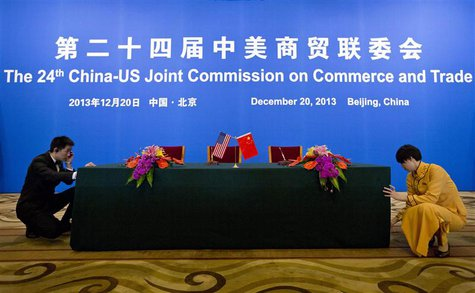 An usher and a hostess prepare a table for a signing ceremony after a meeting of the 24th China-U.S. Joint Commission on Commerce and Trade