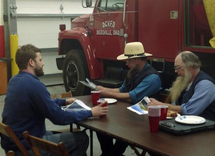 Austin Eudaly (L), an executive with Flatiron Energy Partners, talks with members of the Ohio Amish community at the Deersville, Ohio, Volun