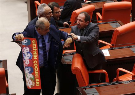 Turkey's ruling Ak Party (AKP) lawmaker Omer Faruk Oz (R) tries to stop Republican People's Party (CHP) lawmaker Musa Cam as he holds a bann
