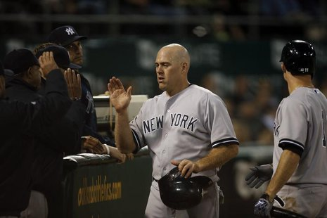 New York Yankees' Kevin Youkilis (C) high fives teammates after scoring from a single by Jayson Nix during the seventh inning against the Oa