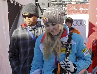 Lindsey Vonn (front R) of the U.S. and her boyfriend, golfer Tiger Woods leave after the Women's World Cup Downhill skiing race in Val d'Ise