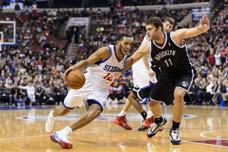 Dec 20, 2013; Philadelphia, PA, USA; Philadelphia 76ers guard Evan Turner (12) is defended by Brooklyn Nets center Brook Lopez (11) during t