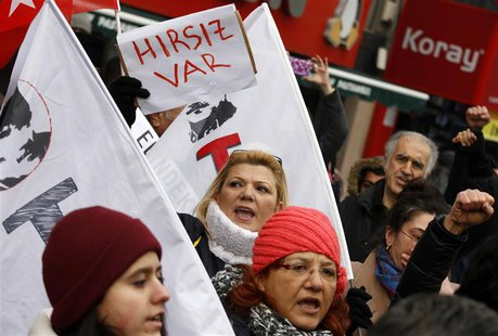 "A woman holds a sign that reads ""There is a thief"" as protesters demonstrate against Turkey's ruling Ak Party (AKP) and Prime Minister Tayyi"