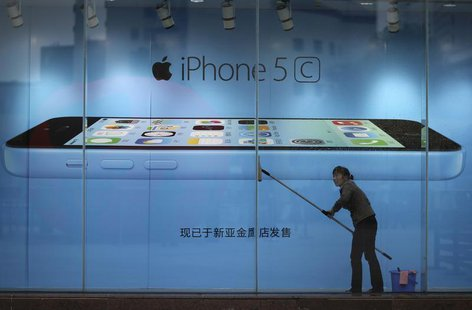 A worker cleans glass in front of an iPhone 5C advertisement at an apple store in Kunming, Yunnan province, in this October 27, 2013 file pi