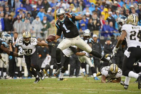 Dec 22, 2013; Charlotte, NC, USA; Carolina Panthers quarterback Cam Newton (1) runs as New Orleans Saints middle linebacker Curtis Lofton (5