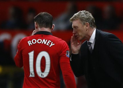 Manchester United's manager David Moyes (R) speaks to Wayne Rooney during their English Premier League soccer match against West Ham at Old
