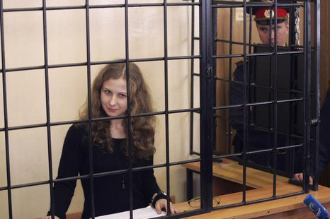 Maria Alyokhina, jailed member of Russian punk band Pussy Riot, looks out from a defendants' box as she attends a court hearing in Nizhny No