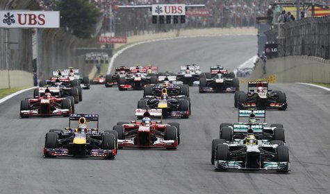 Mercedes Formula One driver Nico Rosberg of Germany (R, front) leads the pack as they head for the first turn at the start of the Brazilian