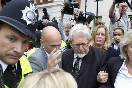 Entertainer Rolf Harris is surrounded by members of the media as he leaves Westminster Magistrates Court, in central London September 23, 20