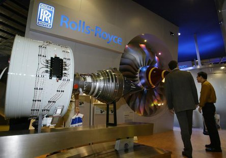 A trade visitor chats with a Rolls-Royce representative at the biennial Asian Aerospace 2004 airshow in Singapore February 25, 2004. . REUTE