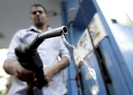 A worker holds up a fuel pump nozzle after filling up the tank of a car at a petrol station in Cairo October 3, 2012. REUTERS/Mohamed Abd El