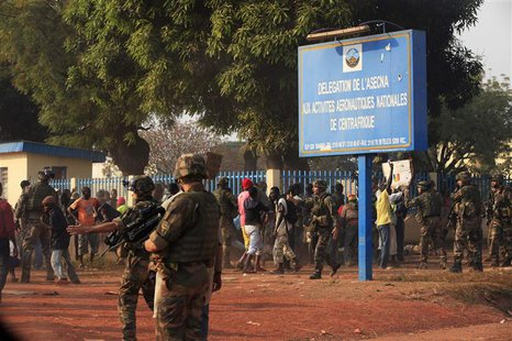 French military personnel try to control supporters who are asking them to disarm fighting gangs, near the airport in Bangui December 23, 20