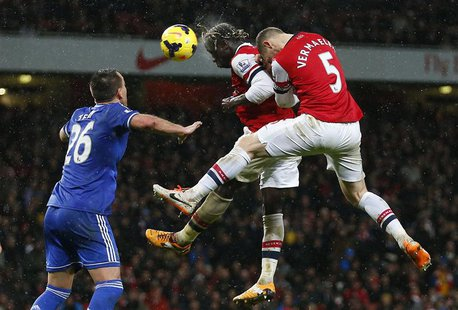 Arsenal's Bacary Sagna (C) and Thomas Vermaelen (R) jump to head the ball as Chelsea's John Terry looks on during their English Premier Leag
