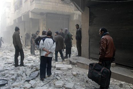 People stand on the rubble of damaged buildings after what activists said was an air raid by forces loyal to Syrian President Bashar Al-Assa