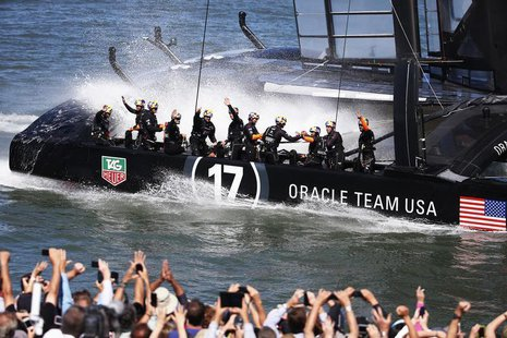 Members of Oracle Team USA wave to spectators after winning Race 16 of the 34th America's Cup yacht sailing race against Emirates Team New Z