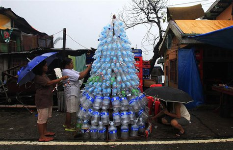 Victims of super Typhoon Haiyan decorate their improvised Christmas tree with empty cans and bottles at the ravaged town of Anibong, Tacloba