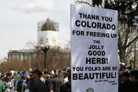 A man holds a sign referring to Colorado legalizing marijuana with the state capitol dome in the background at the 4/20 marijuana holiday in