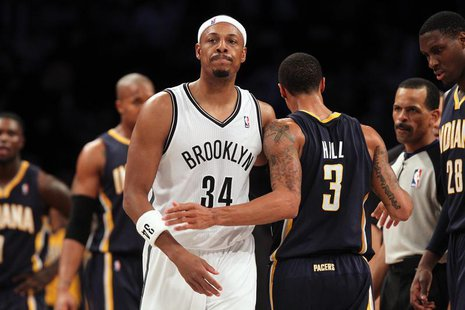 Brooklyn Nets small forward Paul Pierce (34) and Indiana Pacers point guard George Hill (3) walk past one another after Pierce was called fo