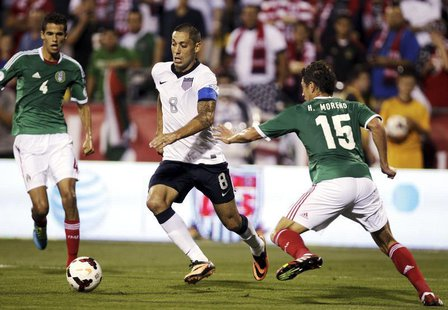 United States' midfielder Clint Dempsey (8) takes the ball past Mexico's Diego Reyes (4) and Hector Moreno (15) during the first half of the
